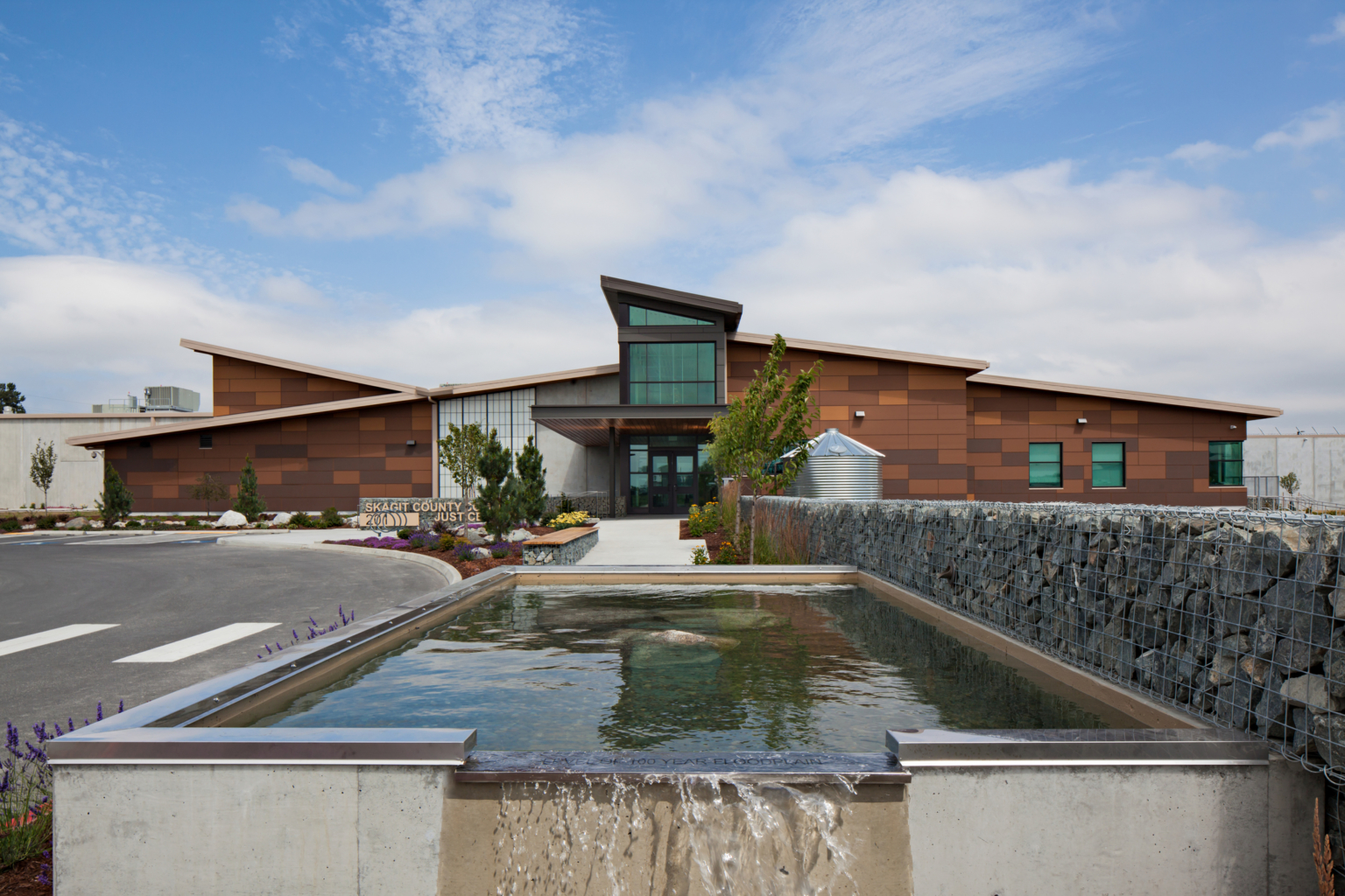a water feature next to a stone gabion in front of a stone and glass building